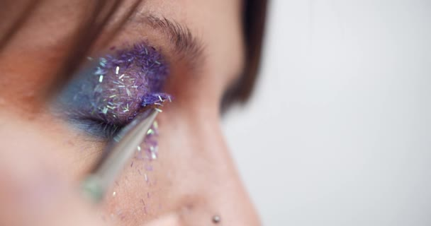 Glitter are applied to the womans eyelid, making of the evening makeup, eyes makeup, makeup artists work, close up makeup