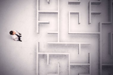 Confused businessman standing at a maze wall
