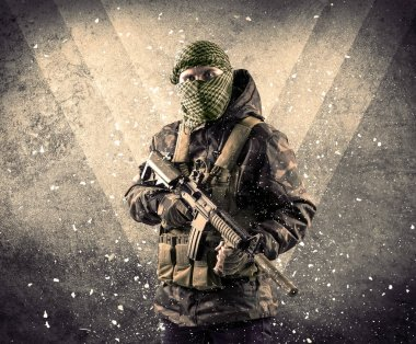 Portrait of a dangerous masked armed soldier with grungy backgro