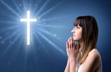 Young woman praying on a blue background with a sparkling cross above her stock vector