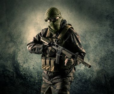 Portrait of a heavily armed masked soldier with grungy backgroun