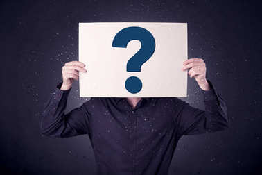 Businessman holding paper with question marks