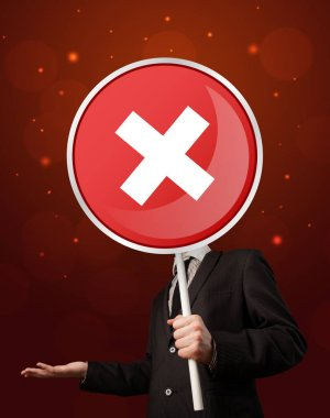 Smart businessman holding round red sign with a white cross stock vector