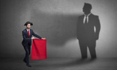 Businessman with toreador concept and his shadow on the background