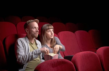 Young couple sitting at red movie theatre