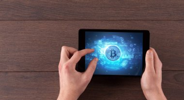 Hand working on tablet with cryptocurrency concept