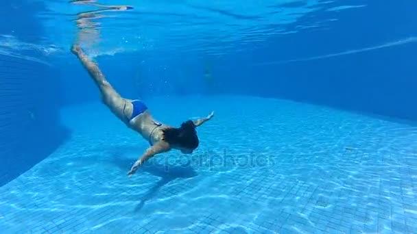 mladá dívka, plavání pod vodou v modré fondu