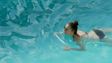 Girl in a black bathing suit and sunglasses
