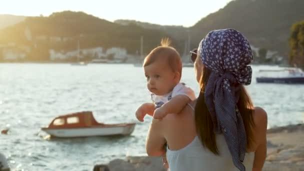 matka vyvolává a otočí malého syna na pláži při západu slunce