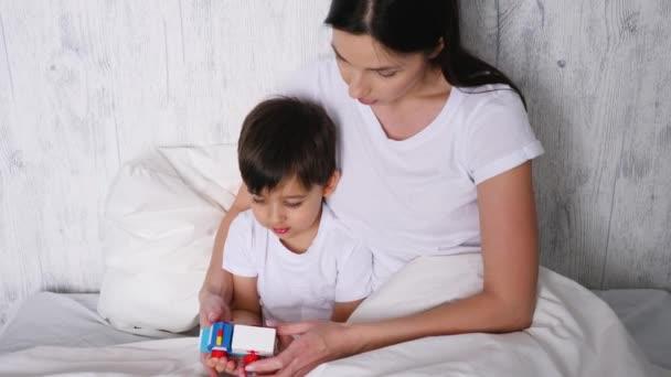 matka a syn sedí na bílé posteli a drží dřevěnou sanitku