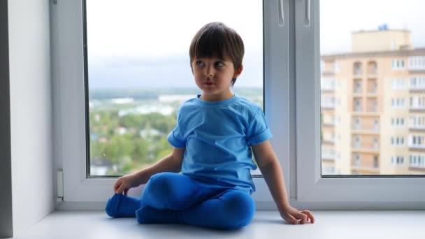šťastný dítě v modrém tričku a punčocháče sedí na parapetu