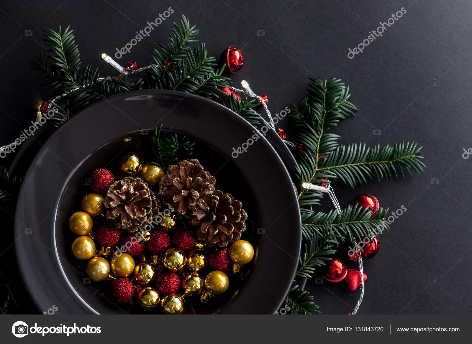 christmas decorations in the black plate on the dark background with some spruce twigsredgold balls and cones inside and christmas light around