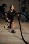 Bruneta žena fitness Ems dělá crossfit trénink pomocí lana. G