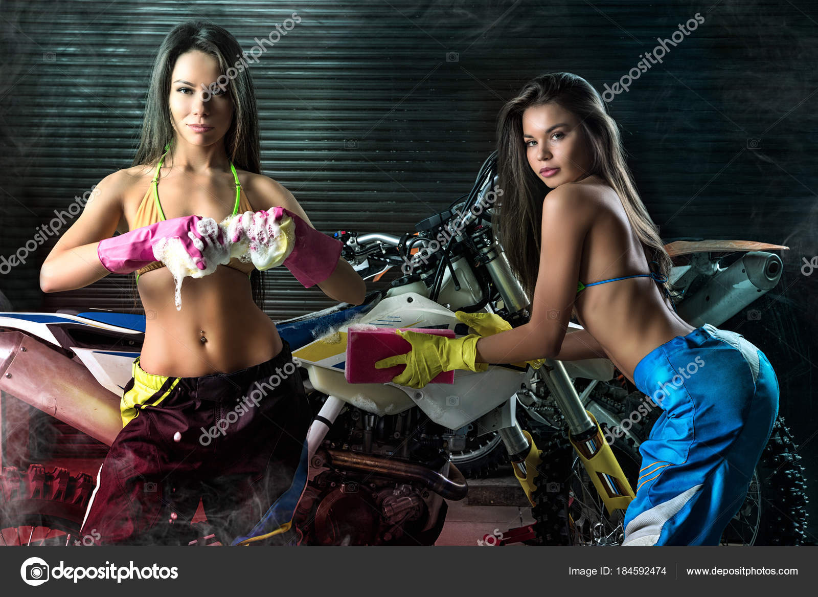 Sexy young models washing motorcycle — Stock Photo