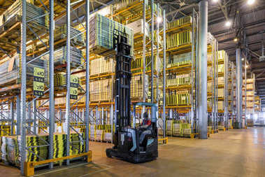 Worker loads goods in a large warehouse