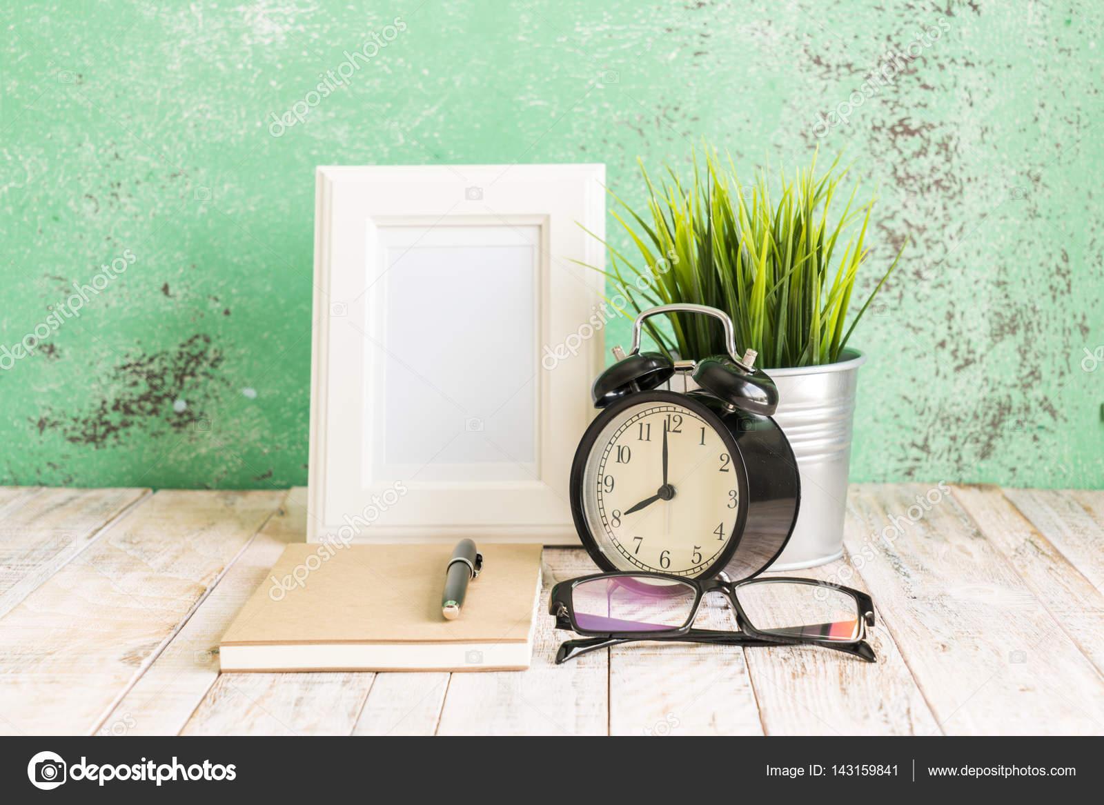 Hölzerne Arbeitsplatz Desktop mit Uhr; Pflanzen; Brille; Rahmen und ...
