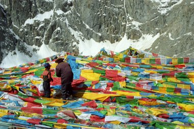 Tibetan pilgrims father and son are hanging the prayer flags Lungta on Drolma La Pass.