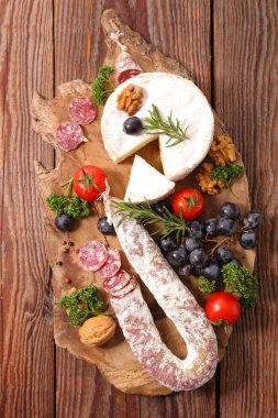camembert and snacks on wooden board