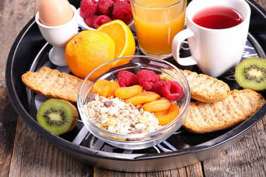 healthy breakfast with tea,egg and cereal on wooden table
