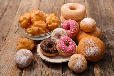 Close-up view of assorted donuts and pastries  on wooden table