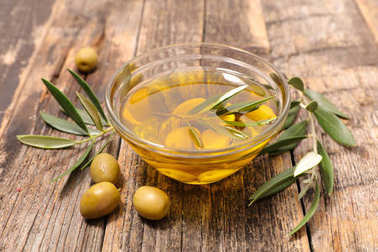 olive oil in glass bowl with olives and olive branches