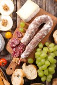 Fotografie wooden cutting board with salami and cheese with grape on table