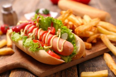 delicious hot dog with french fries on wooden board