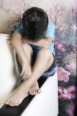 Osamělý chlapec smutně sedí na sedáku pohovky