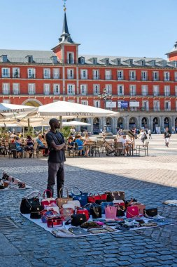 Madrid, Spain - 20 July 2018: Madrid city center, illegal vendor migrant selling fake bags