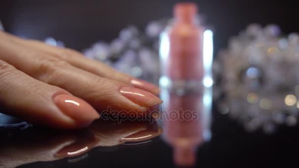 Finger nail care by manicure specialist in beauty salon. Girl paints nails.