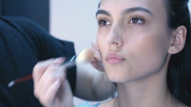 Maskérka aplikovat make-up na atraktivní mladé ženy