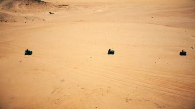 Skyline Aerial view of young men riding quad bikes over sand dunes in desert.