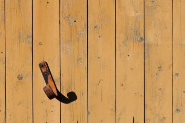 Rusty metal hook on the wall from boards background