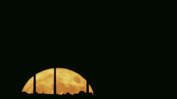 Full moon moving behind the horizon with silhouettes