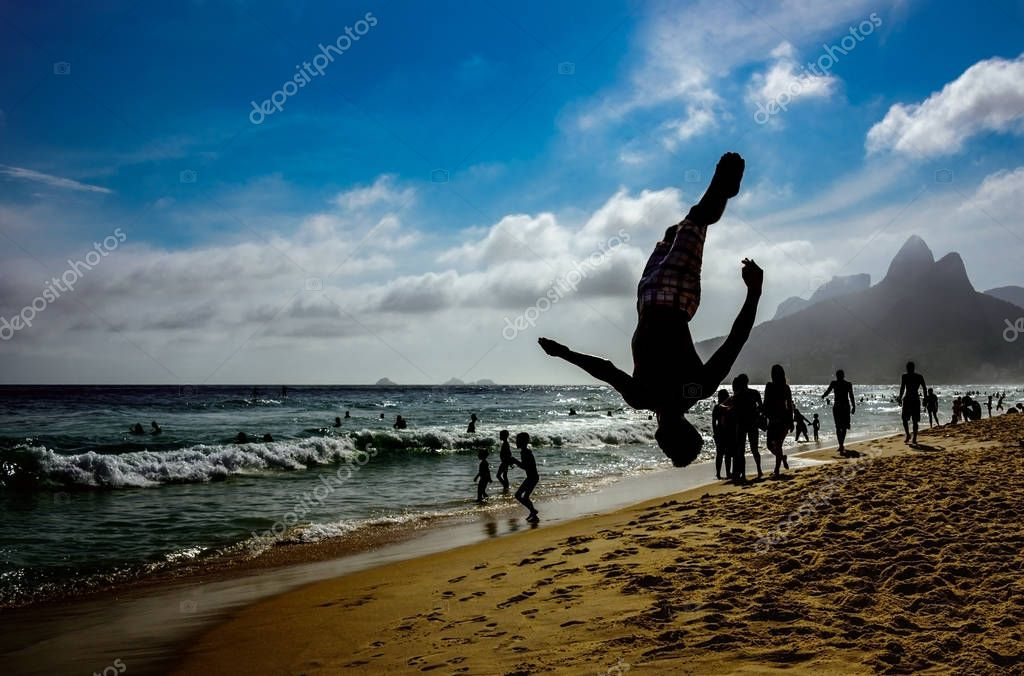 Silhouette of the man perfoming a back somersault in pike position at Ipanema beach, Rio de Janeiro, Brazil