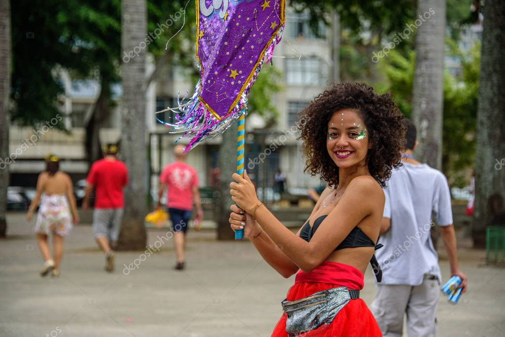 Beautiful smiling woman with curly hair and nose piercing, holding purple flag at Bloco Orquestra Voadora, Carnaval 2017