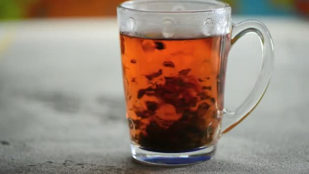pile of natural ceylon black tea mix with hibiscus flower brewed in glass cup on colorful background