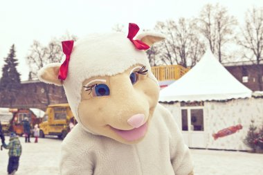 The man dressed as a white sheep on the street in winter.