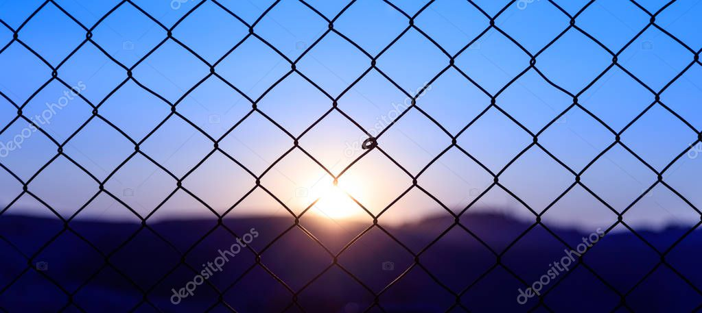Wire mesh fence on a sunset background