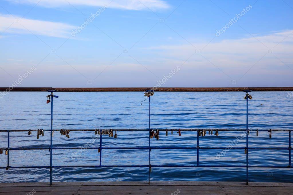 Rusty padlocks has been locked on a peeled railing of platform. Blue sky and sea background.