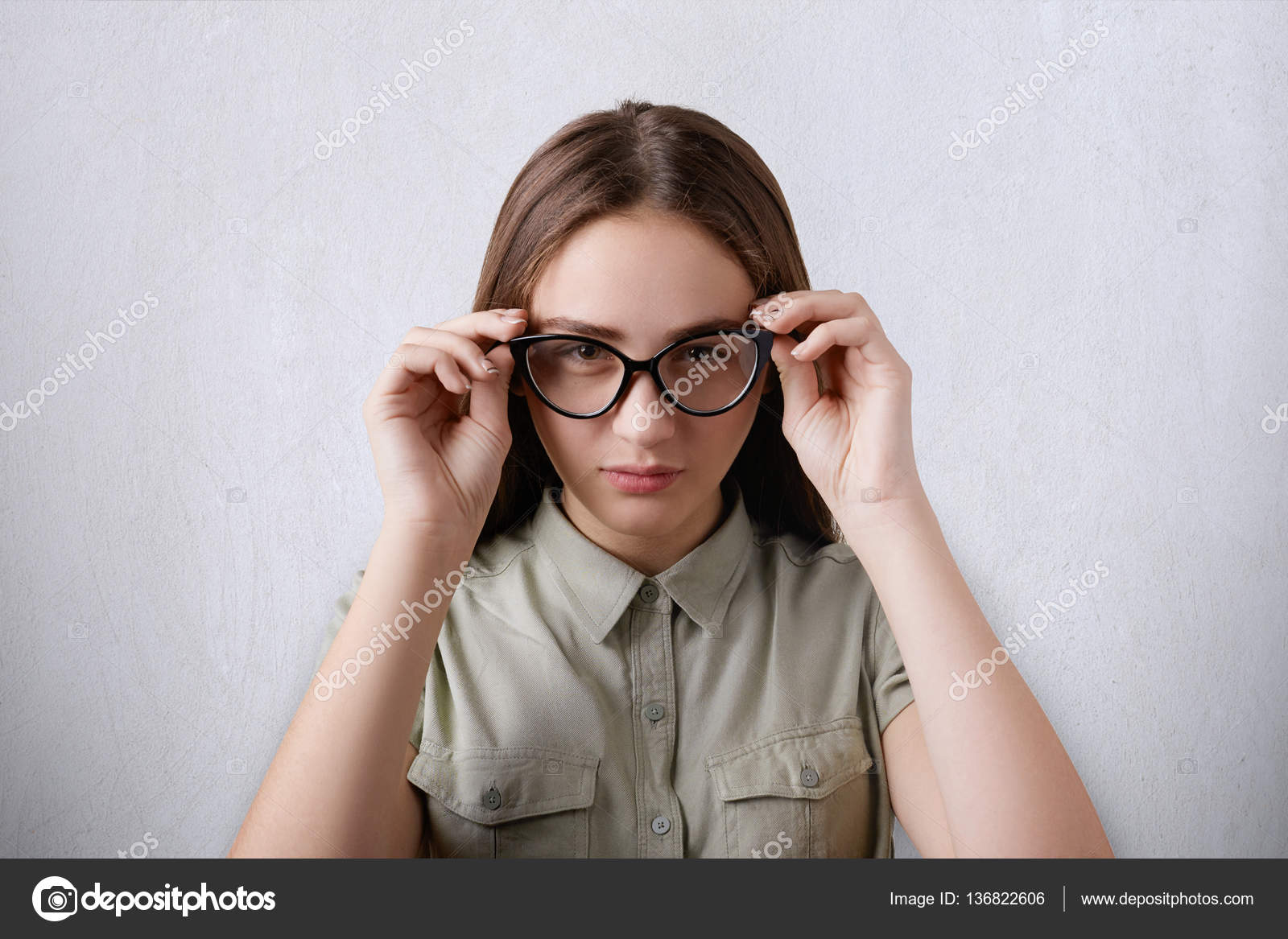 1bac485dc57 A portrait of beautiful girl wearing shirt having long hair isolated over  grey background wearing big glasses touching her glasses with her hands  having a ...