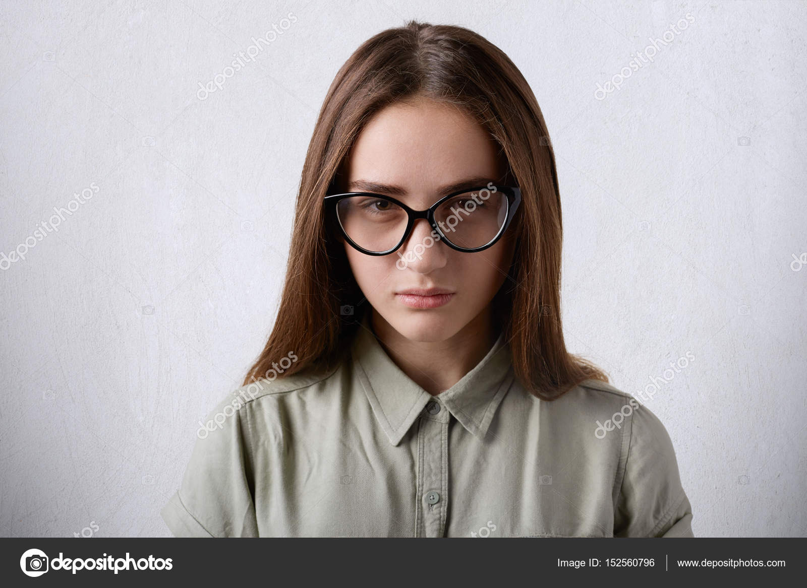d86394f4ea Un retrato de bastante joven colegiala teniendo pelo liso largo castaño  lleva camisa elegante y anteojos piercingly mirando a la cámara aislada  sobre fondo ...