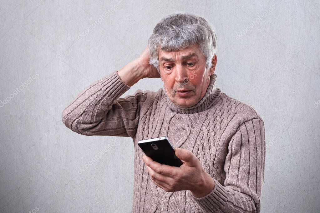 A shocked mature man holding mobile phone touching his head with a hand. An elderly person with gray hair being astonished while looking into his phone. People and emotions. Receiving bad news.