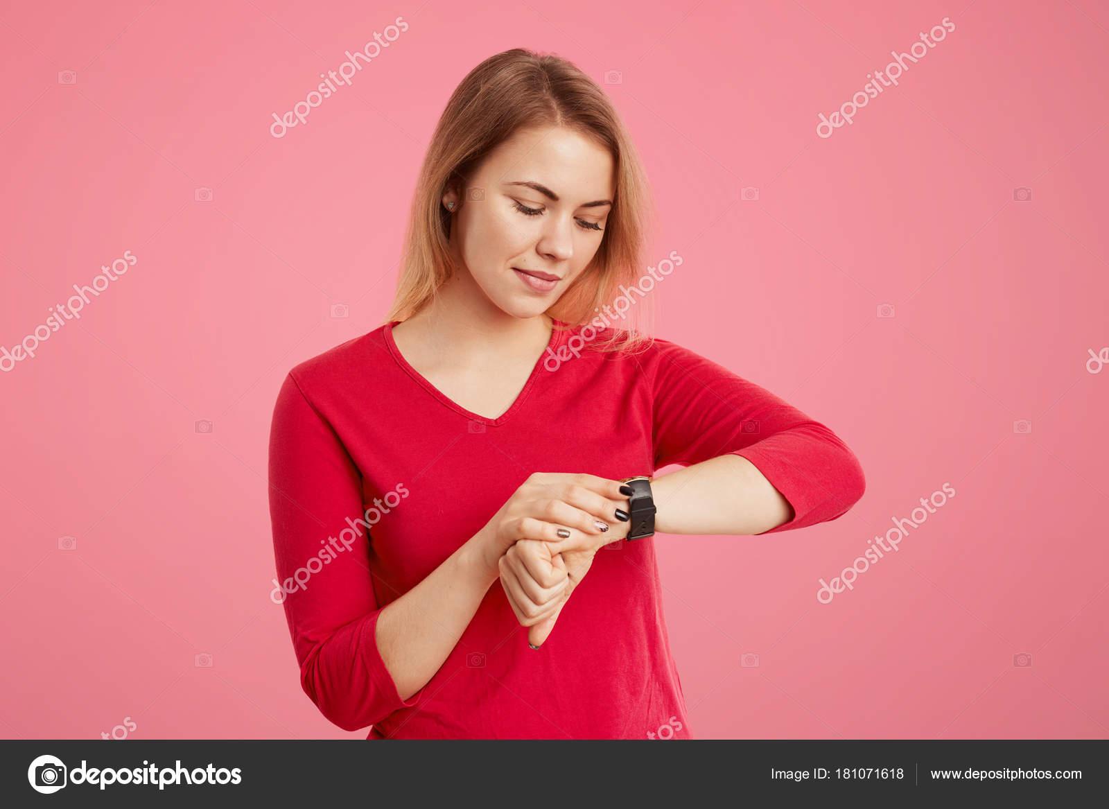 Jeune femelle a look attrayant vérifie l heure sur sa montre