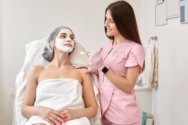 Horizontalshot of beautiful woman receiving spa treatment. Cosmetologist in beauty salon cleaning woman's face, applying cream with special brush. Youth, skin care, aethetic medicine concept.