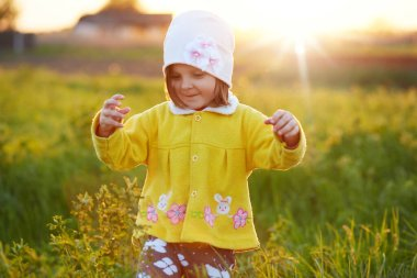 Picture of happy female kid wearing yellow jacket and white cap playing in meadow, child surrounded flowers and grass, girl keeping hands up, playing in field during sunset. Childhood concept.