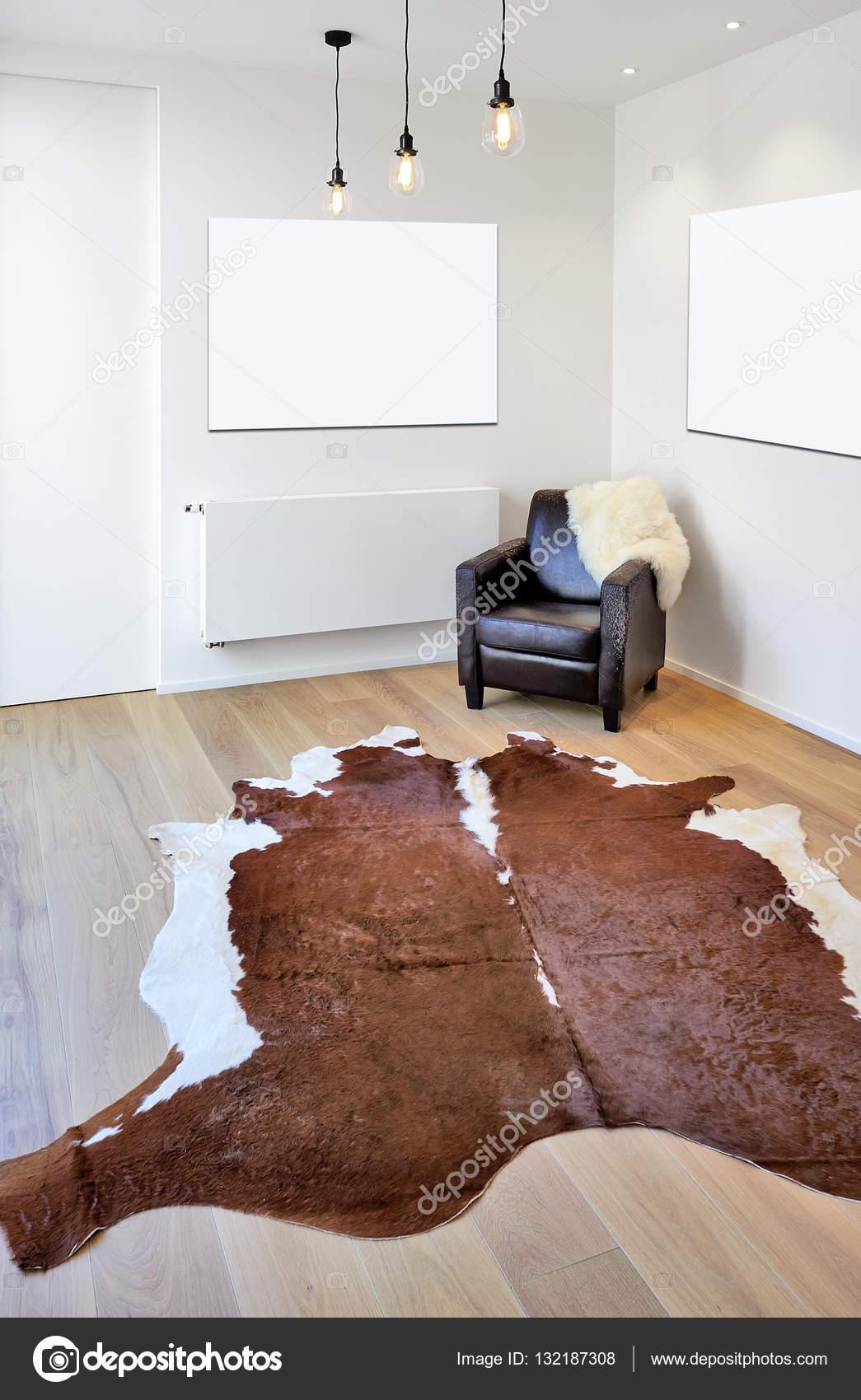 Tappeto di mucca e poltrona il nuovo pavimento in legno — Foto ...