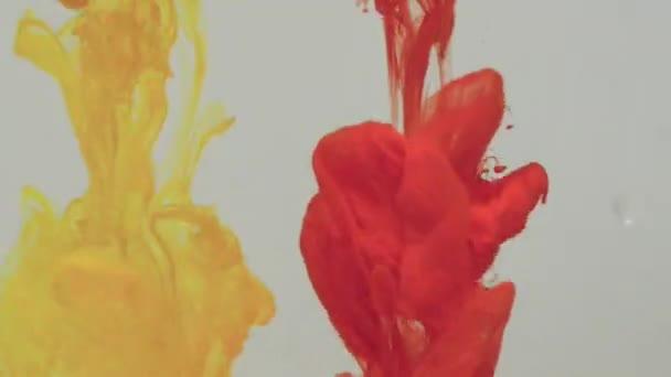 Přechod žluté a červené barvy inkoustu upustil do vody