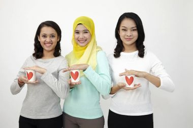 three multi racial malaysian holding cup of love looking at camera