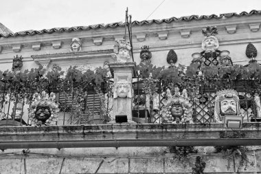 Italy, Sicily, Palazzolo Acreide (Syracuse Province); ceramic statues and plants on the balcony of a Liberty palace in a central street of the town